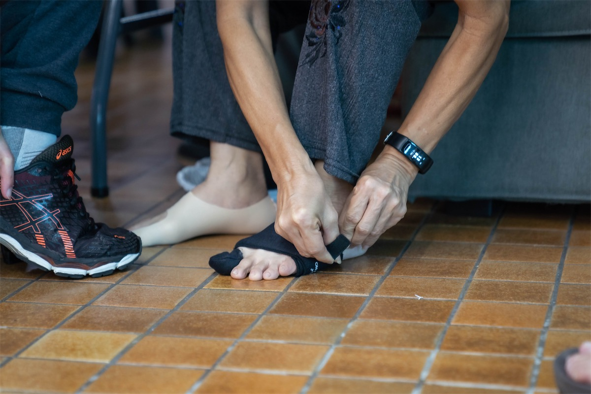 person putting a bunion corrector on his feet